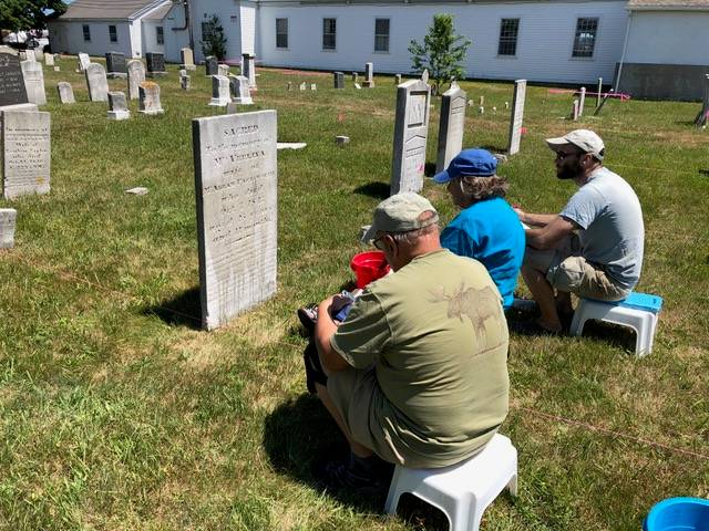 People studying an old headstone